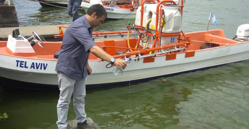 Un representante de la empresa israelí echa el líquido en el Lago de Amatitlán.