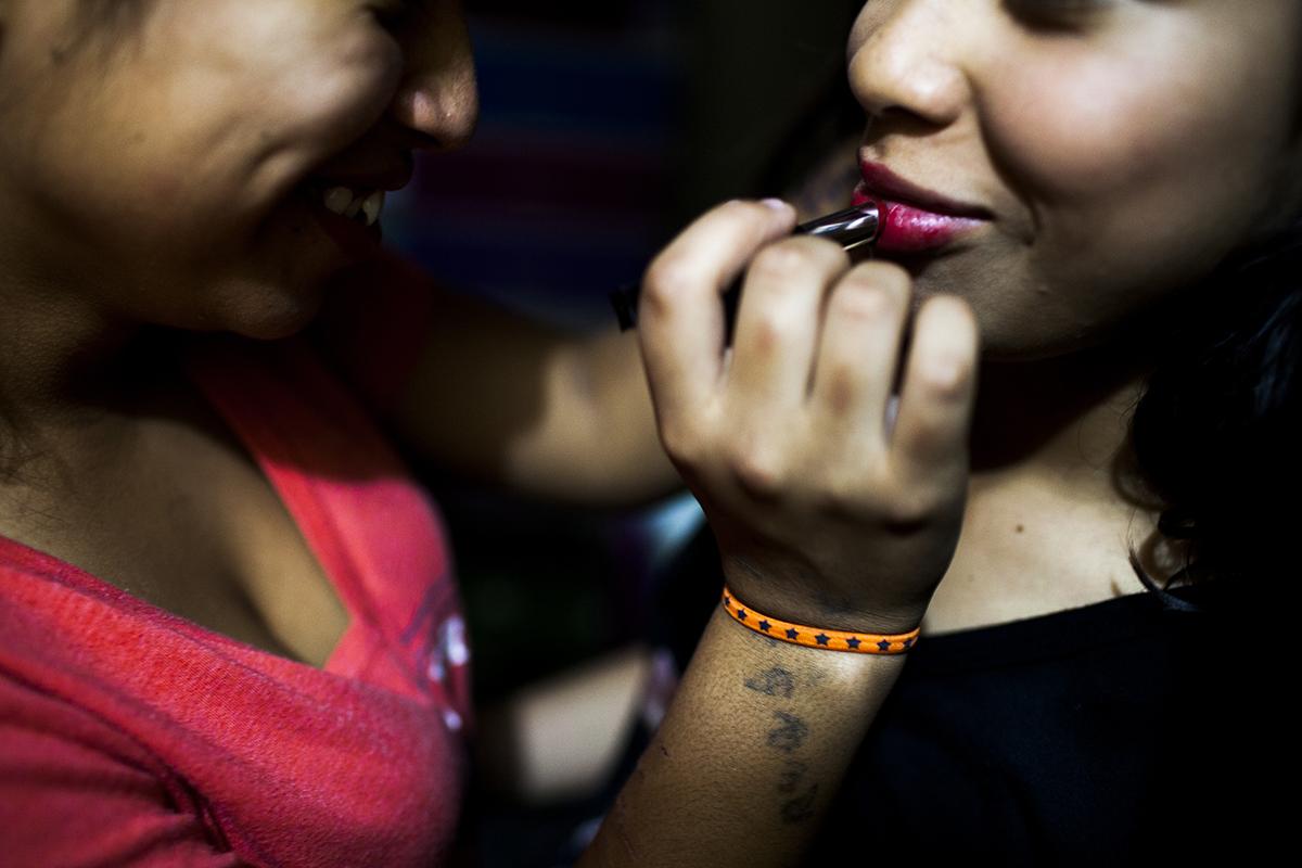 Durante una noche cultural, una adolescente pinta los labios de otra compañera.