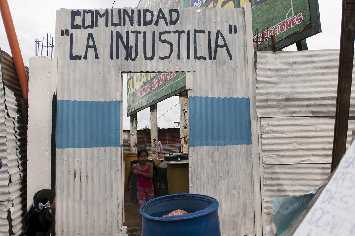 """La comunidad """"La Injusticia"""" se lee en una de las entradas del asentamiento."""