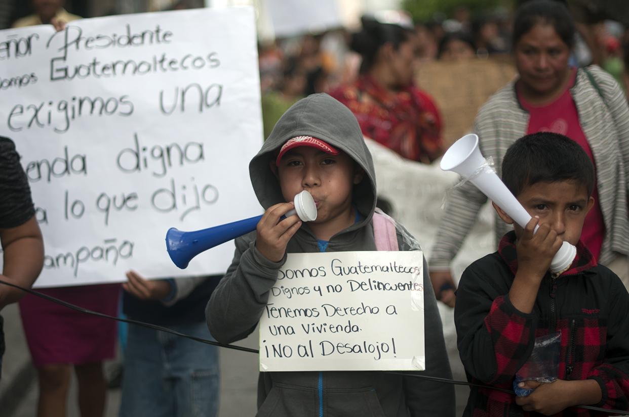 Niños y adultos piden el no desalojo y una vivienda digna.