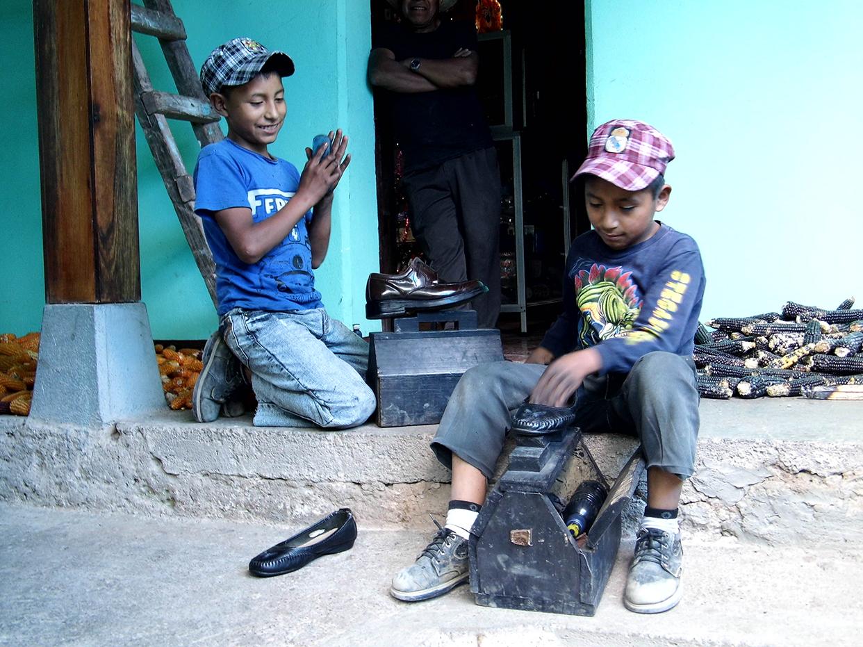 Miguel (izquierda) y Paulino lustran los zapatos de dos clientes.