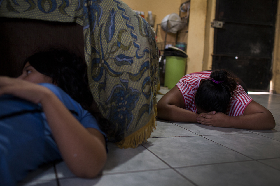 Tiradas al suelo, Magdalena y Saraí esperan que termine el estruendo de las balas