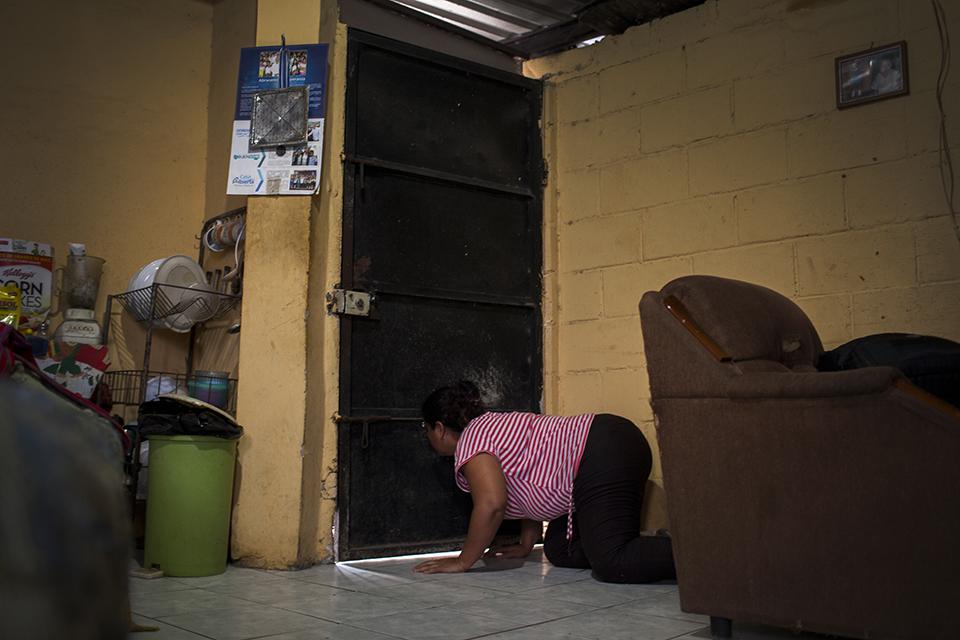 Magdalena se asoma a la puerta para mirar la escena afuera de su casa