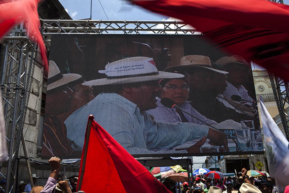 En una pantalla gigante frente al congreso, los manifestantes aplauden el discurso de Daniel Pasqual, leader del CUC