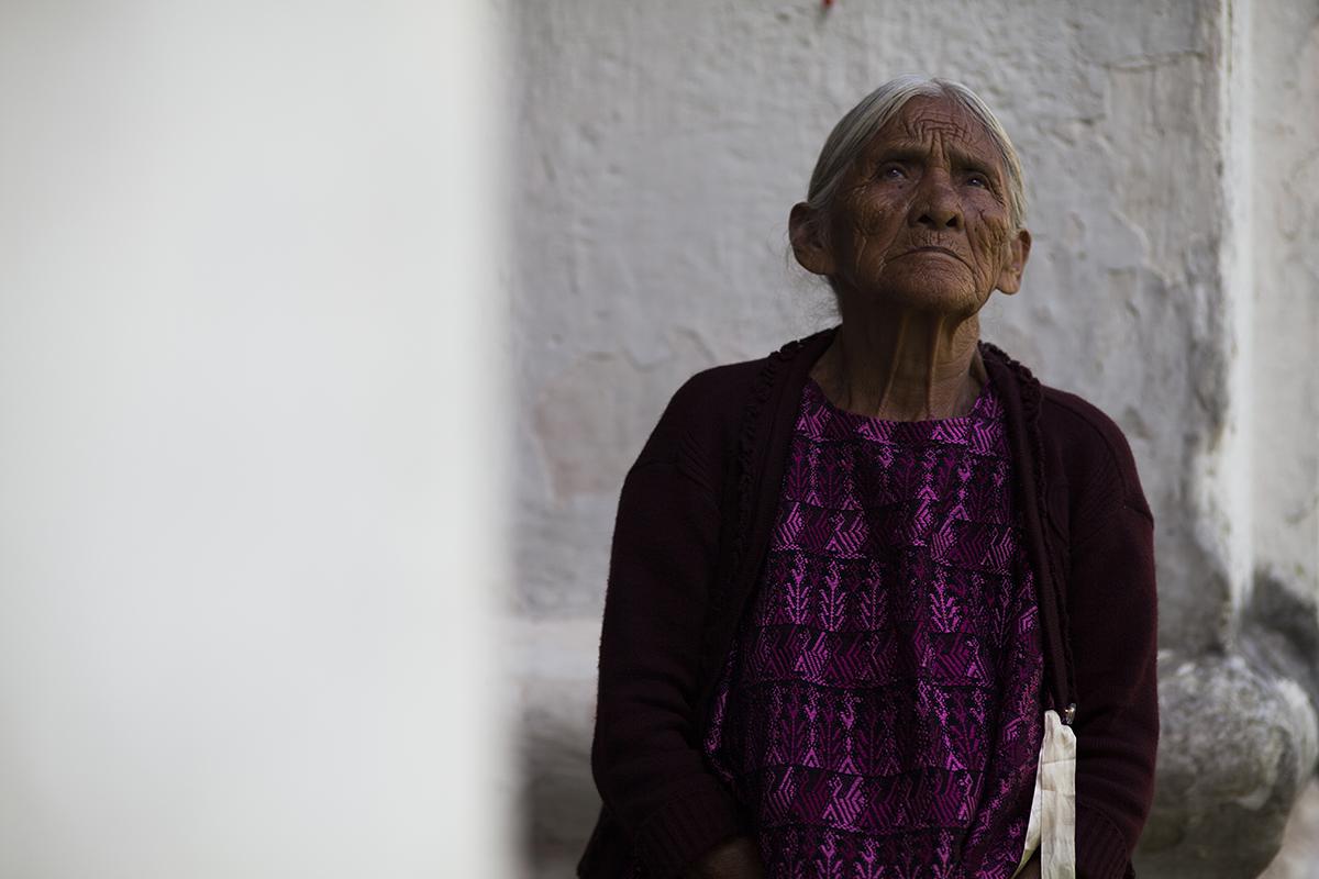 Una anciana, familiar de una de las ocho víctimas exhumadas, espera su turno para poder acompañar su difunto a la casa