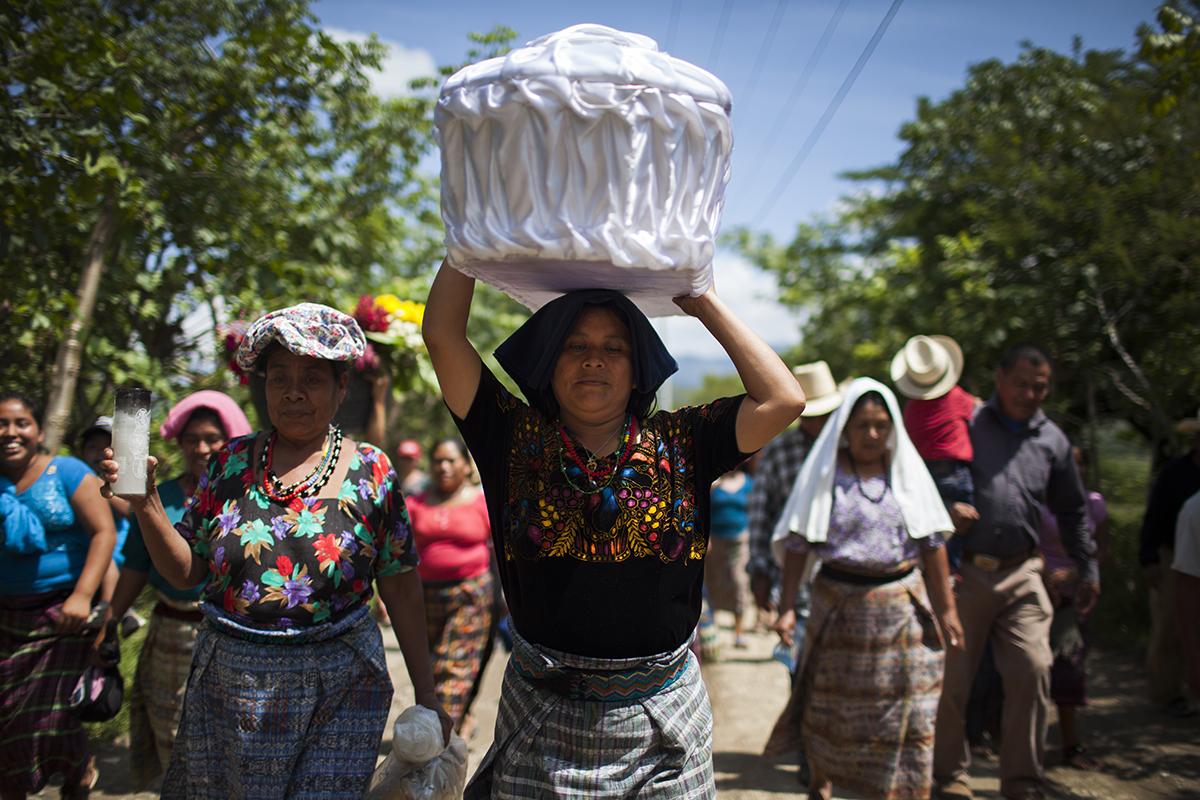 Clara Osorio, 40, prima de Marta Elena, transporta el ataúd a la casa de la familia para el velorio, en el caserío Pacux del municipio de Rabinal
