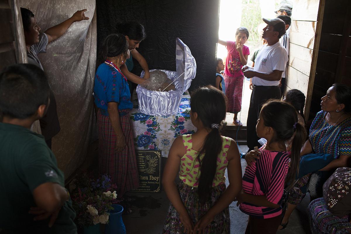 En la casa, los familiares rodean el ataúd mientras una antropóloga forense de la Fundación de Antropología Forense de Guatemala - FAFG - recompone las osamentas de Marta Elena