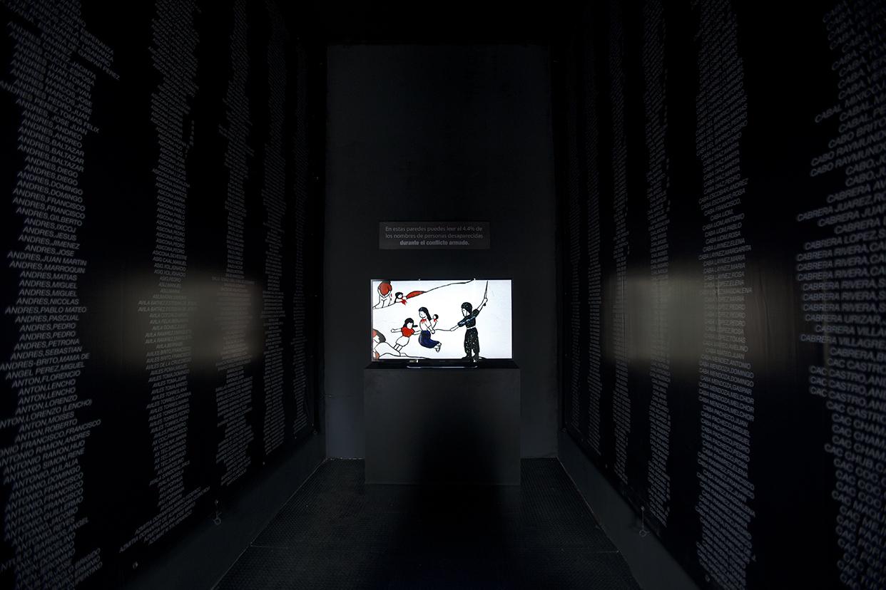En una sala se proyecta un video que documenta la vida de las comunidades de población en resistencia. A lado los nombres de 2,190 víctimas del conflicto armado, que representa el 4.4 por ciento del total de los masacrados.