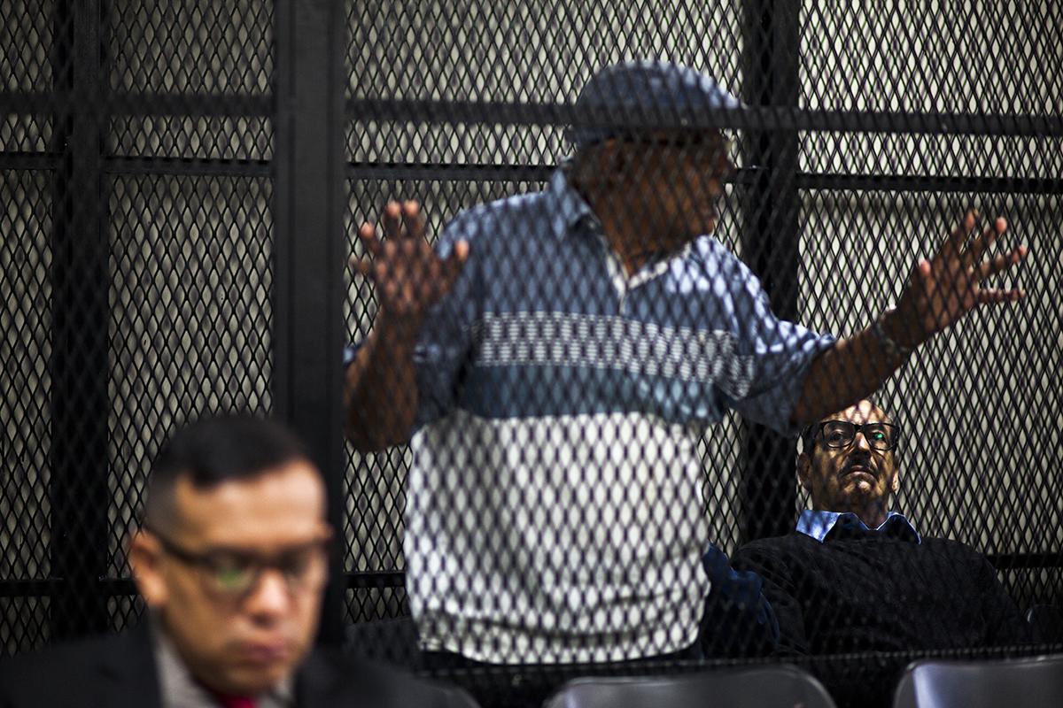 Hugo Ramiro Zaldaña Rojas observa a Benedicto Lucas García, exjefe de  Estado Mayor del Ejército, asomarse a las rejas para escuchar al juez.