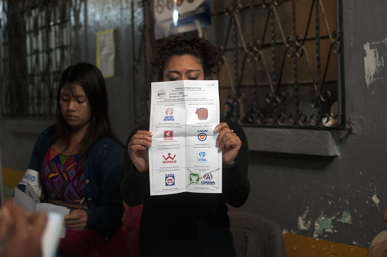 La presidenta de una de las mesas muestra una de las boletas con voto para la UNE-GANA