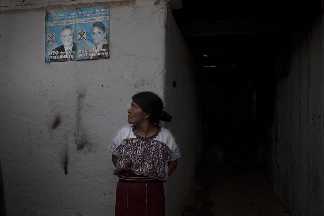 Rosa Santiago mira los afiches electorales del Partido Patriota pegados desde hace dos años en la pared de su casa.