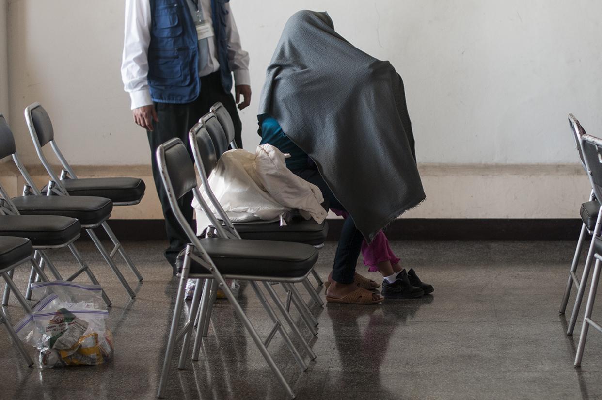 Una madre y su hijo se cubren luego de su llegada en un avión de deportados desde los Estados Unidos el pasado viernes. Foto de Sandra Sebastián