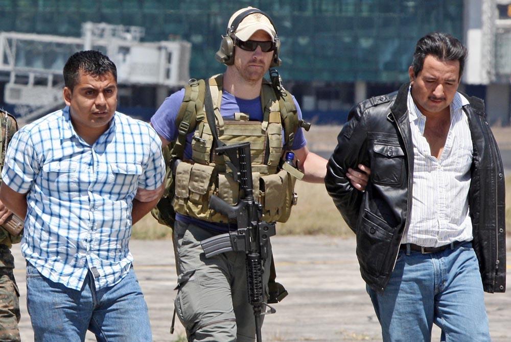 Foto de la captura del supuesto capo Juan Chamalé (derecha), llevado del brazo por un agente estadounidense en el Aeropuerto La Aurora.