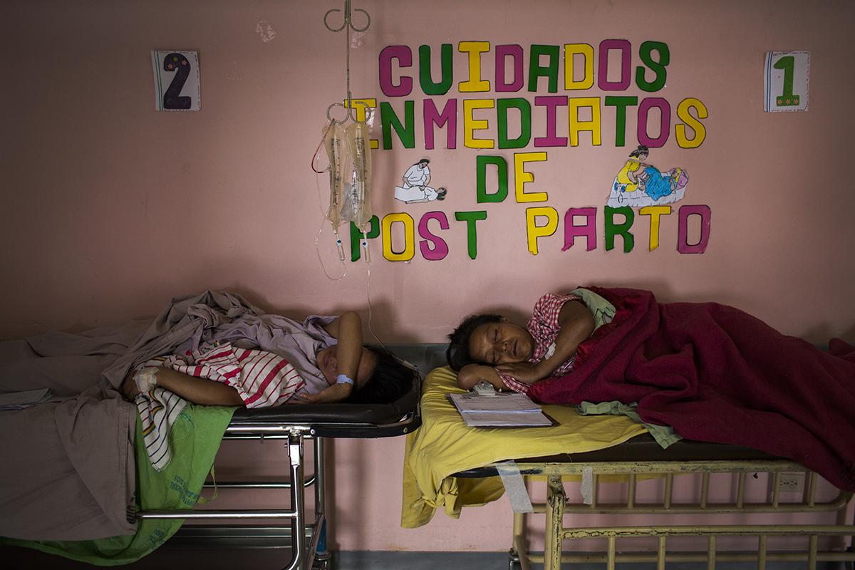 Dos mujeres en sus camillas después de haber dado a la luz en el área  de  maternidad  del  hospital  San  Juan  de  Dios.