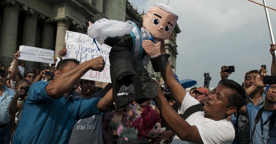 Los asistentes golpean una piñata que representa al presidente Otto Pérez Molina.