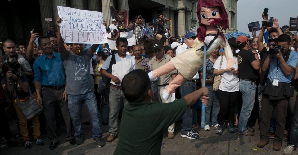 Un niño quiebra una piñata que representa a la vicepresidenta Roxana Baldetti.