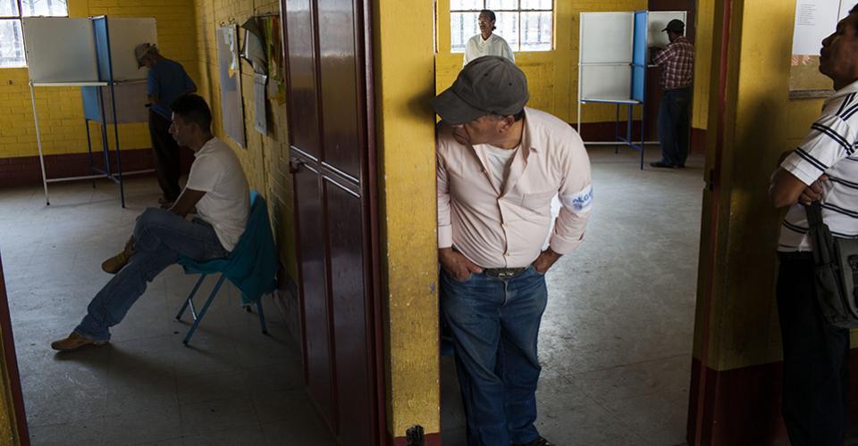 Un alguacil voluntario custodia la entrada a una mesa de votación.