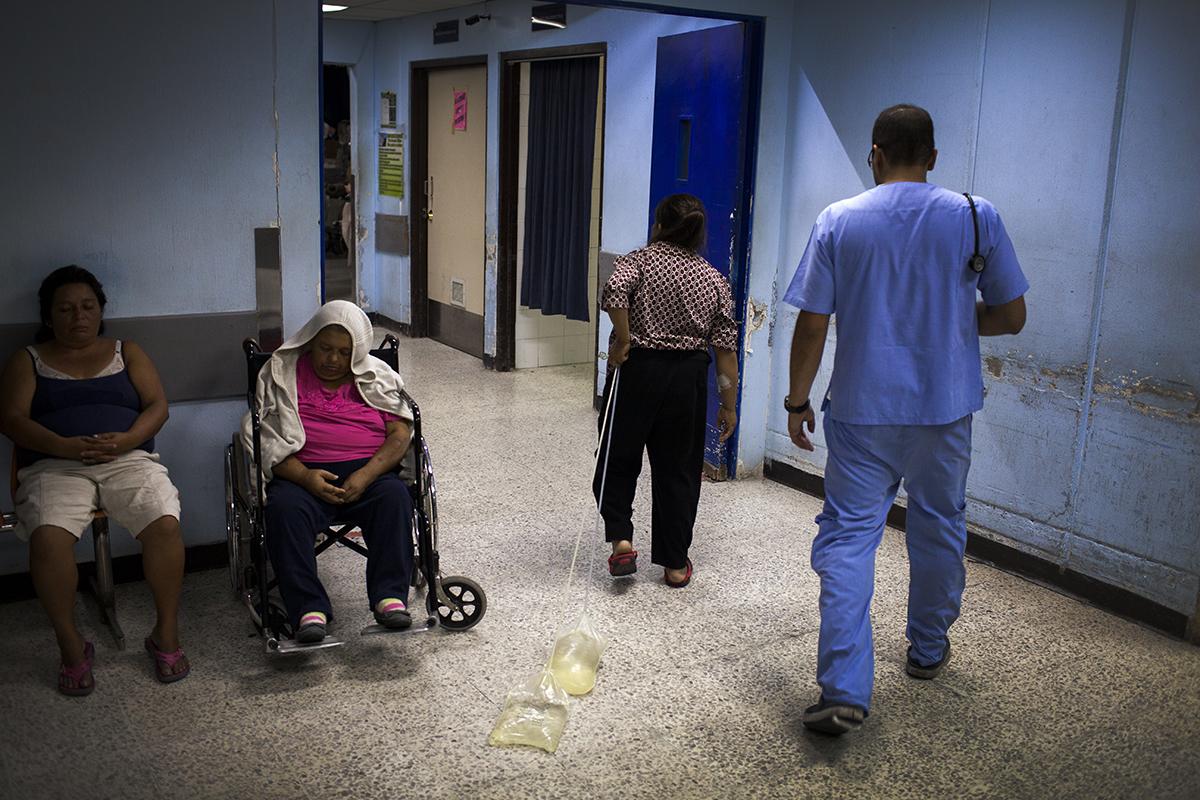 Una paciente arrastra dos bolsas de líquido peritoneal en la entrada de la división de emergencia de adultos