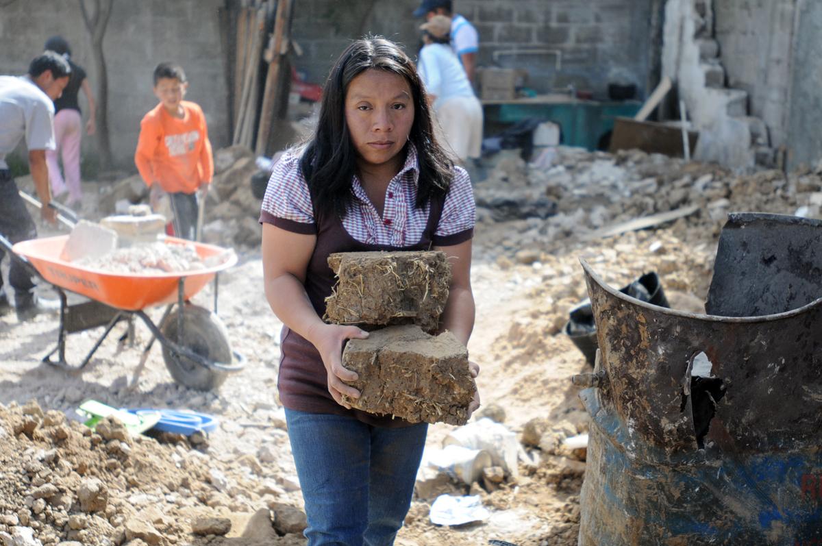 Consuelo Velásquez ayuda a levantar el adobe que formaba su casa.
