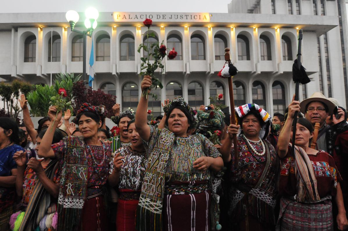Familiares y amigos de víctimas del conflicto armado y autoridades indígenas frente al palacio de justicia.