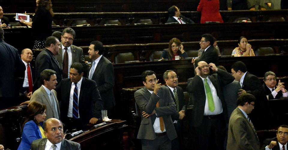 Diputados de varias bancadas observan la pizarra electrónica que marca las votaciones del pleno.