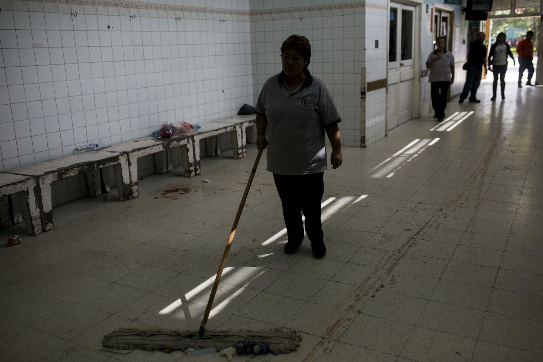 Una mujer limpia un pasillo del Hospital Roosevelt después de la masacre.