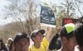 Un joven lleva un cartel con las fotos de las mujeres que impidieron el paso de la maquinaria de la empresa minera.