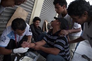 Alfonso, de 26 años, limpia la herida que Alex, de 20, causada en una pelea la noche anterior.