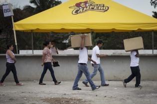 """Un grupo de personas con gafetes de """"coordinadores"""" cargan cajas llenas de comida rápida para proporcionar a los asistentes."""