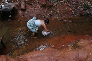 Una mujer recoge agua cerca de la zona de explotación de niquel.