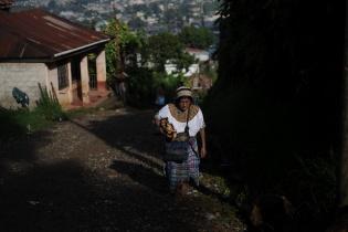 Una mujer q'anjob'al camina hacia su casa.