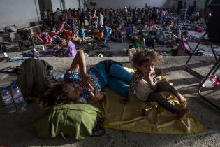 Britany Nieto, 3, hondureña de San Lorenzo, descansa con su mamá en el salón municipal de Niltepec / Simone Dalmasso