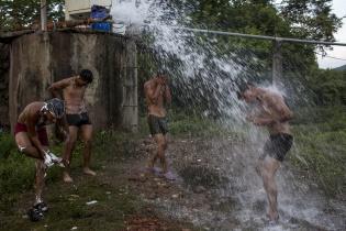 Jóvenes miembros de la barra brava del Olimpia, de Tegucigalpa, se duchan con el agua de una tubería, cerca del río de Niltepec / Simone Dalmasso