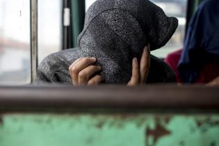 Un migrante cubre el rostro frente al ataque mediático de varios medios de prensa. Acaba de ser trasladado en avión a Guatemala desde Brownsville, Texas, junto con otros 65 connacionales detenidos, el jueves 19. Sienta en un bus militar a la espera de ser trasladado a su comunidad de origen. Simone Dalmasso