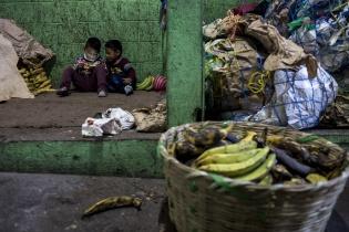 Dos niños, originarios de Santa Cruz El Quiché, juegan en la platanera del mercado de la Terminal, donde trabajan sus padres. Simone Dalmasso