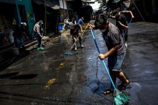 Vendedores de la carbonera, en el mercado de la Terminal, limpian voluntariamente la calle al mediodía del miércoles 18 como medida para prevenir el contagio. Simone Dalmasso