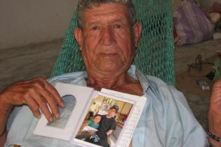 Tranquilino Castañeda sostiene la foto de su hijo, que fue llevado por el ejército cuando éste tenía tres años, en Dos Erres. (Fotografía de Louisa Reynolds)