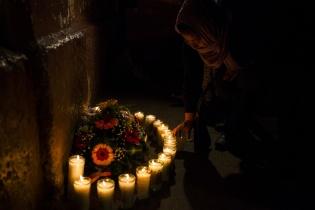 Una joven egresada hace tres años del Hogar Seguro Virgen de la Asunción enciende una vela en homenaje a las 21 niñas fallecidas, en la noche del 08 de marzo.
