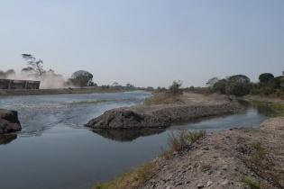Trabajadores del grupo Hame resguardan la entrada del canal que traslada el agua del río a las plantaciones de palma africana (derecha). La empresa abrió nuevamente el canal que fue cerrado la semana pasada por las comunidades.