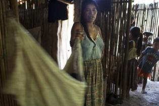 Elvira Ac Má es la mamá de la difunta María Magdalena. Rodeada por niños de la comunidad, María mece el costal en que reposa su bebé recién nacido.