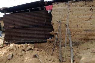 Troncos de árboles sostienen las paredes de abode para que no caigan.