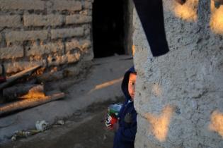 Un niño sostiene una lata de frijoles.