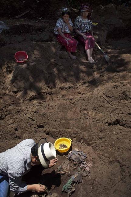 Un arqueólogo de la Fundación de Antropología Forense de Guatemala – FAFG – exhuma los restos de una mujer adulta bajo la mirada de Feliciana y Catarina.
