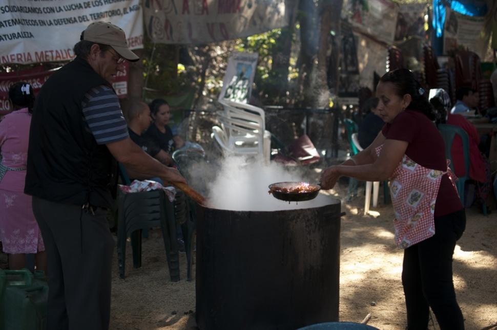 Mujeres y hombres preparan el alimento que le darán a los visitantes.