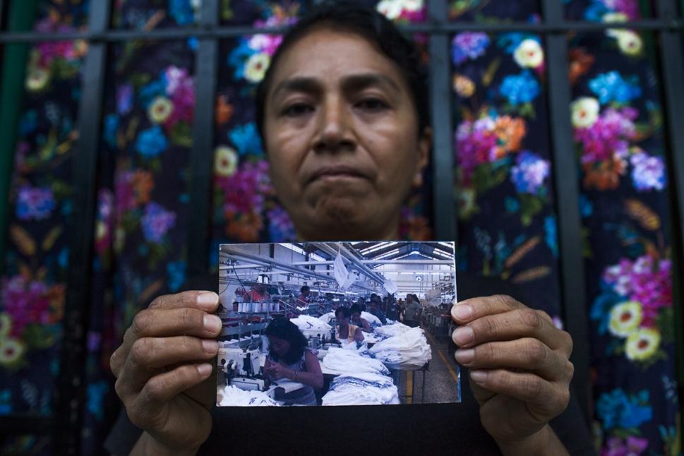 Francisca Alvarado Chij, 47, madre soltera de 2 hijos y abuela de 2 nietos. Muestra una foto sacada en la maquila donde lleva 22 años de trabajar como operaria.