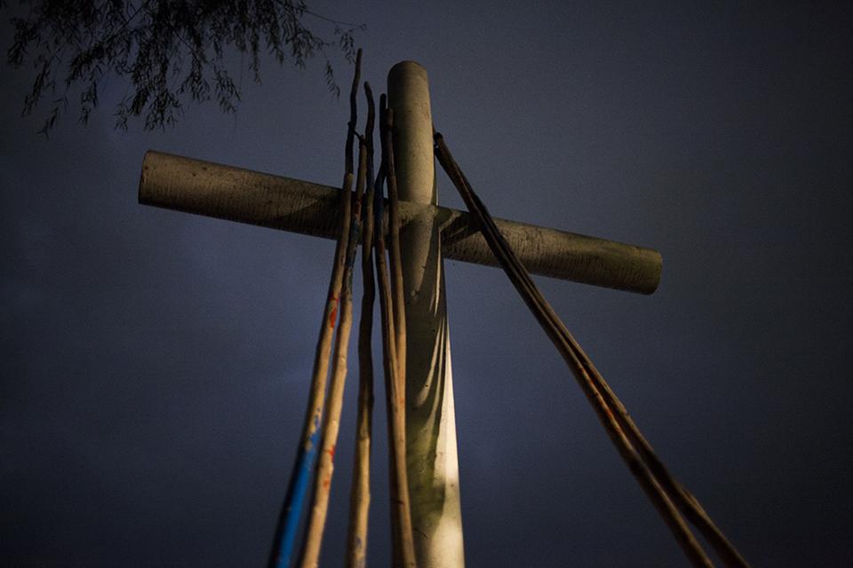 Remos de mangle apoyados encima de la cruz, monumento a los migrantes caídos, al final del día.
