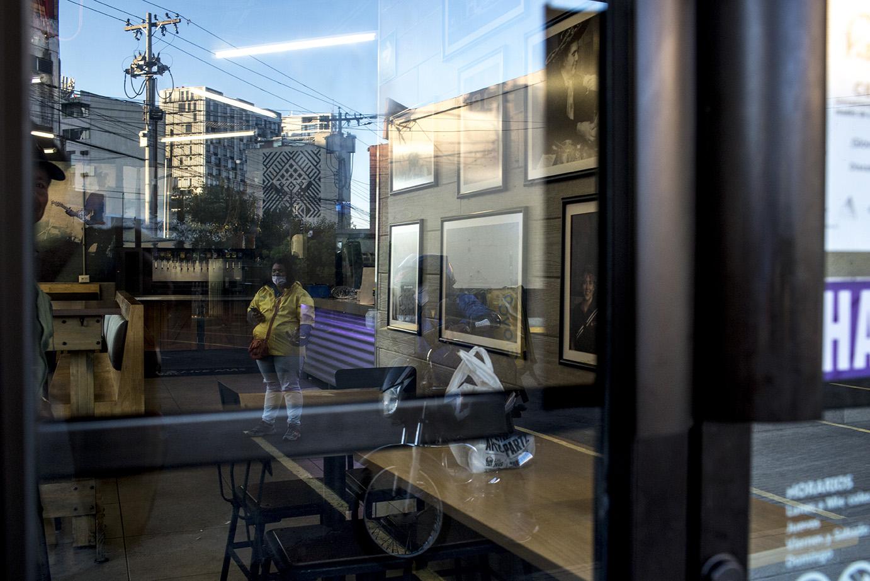 Trabajadores del servicio a domicilio Glovo esperan su pedido frente a la entrada de una famosa cadena de comida rápida. Simone Dalmasso