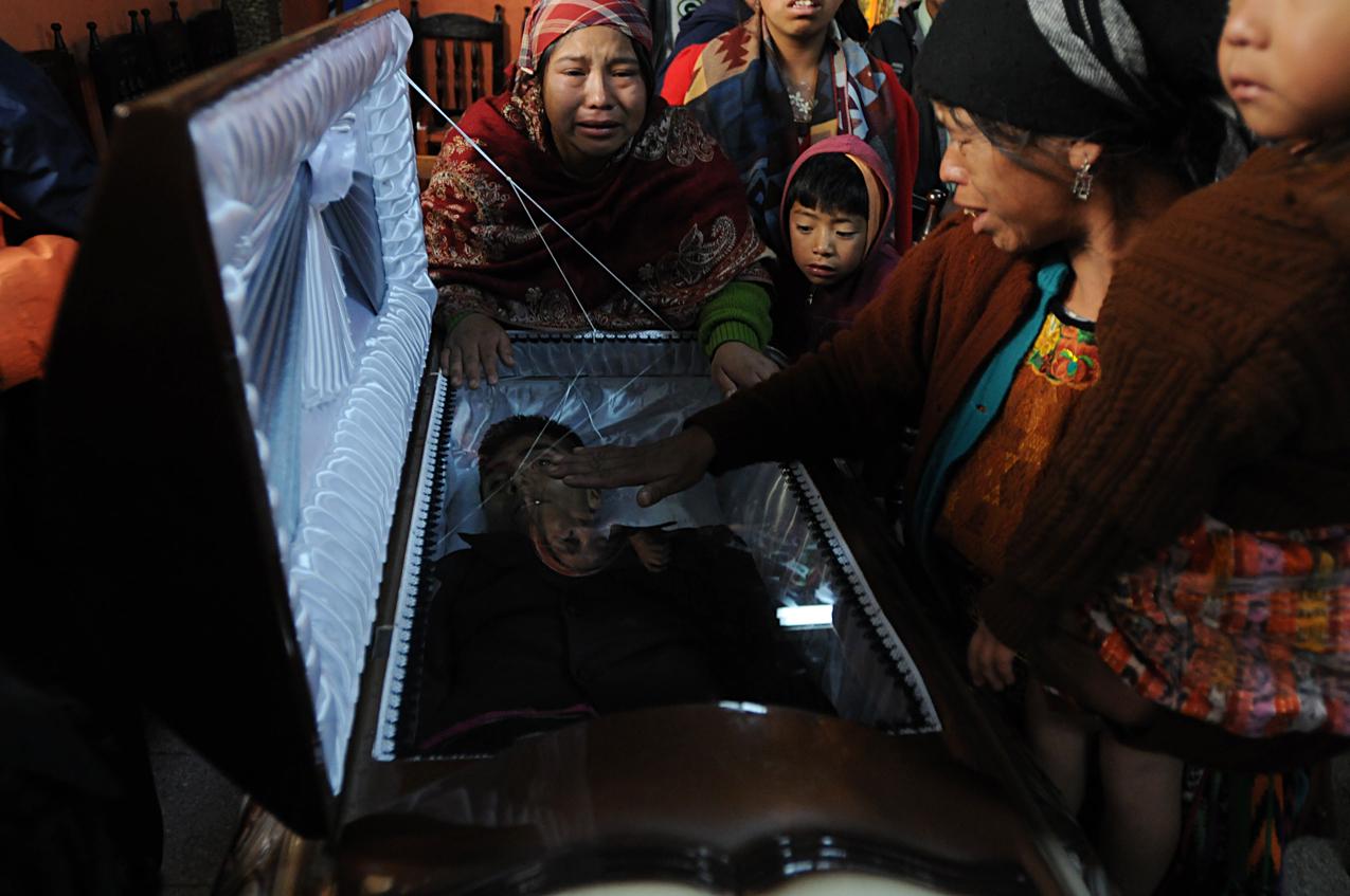 Familiares de Eusebio Puac lloran durante el velorio.