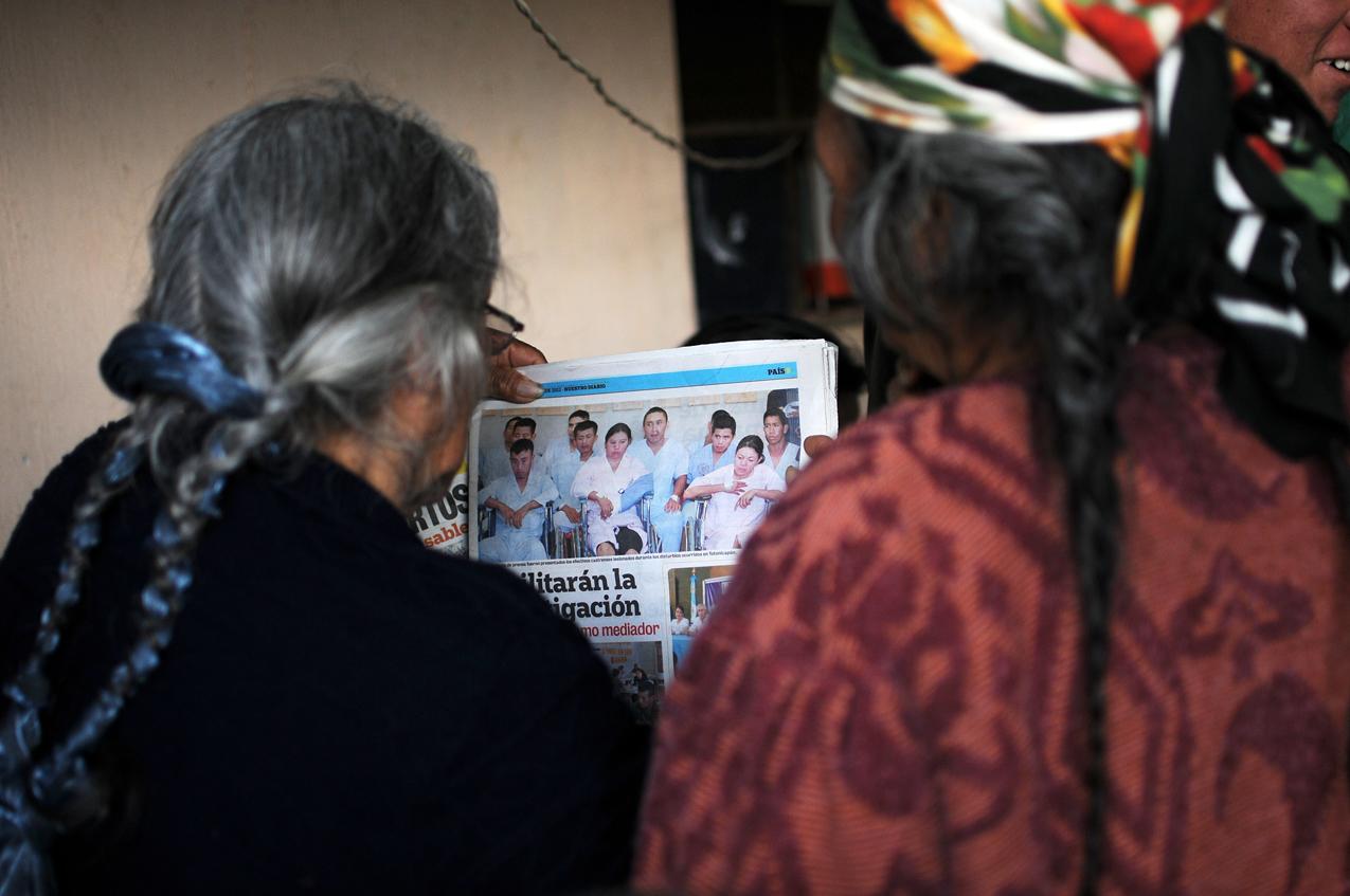 Mujeres ven la foto de efectivos castrenses lesionados.