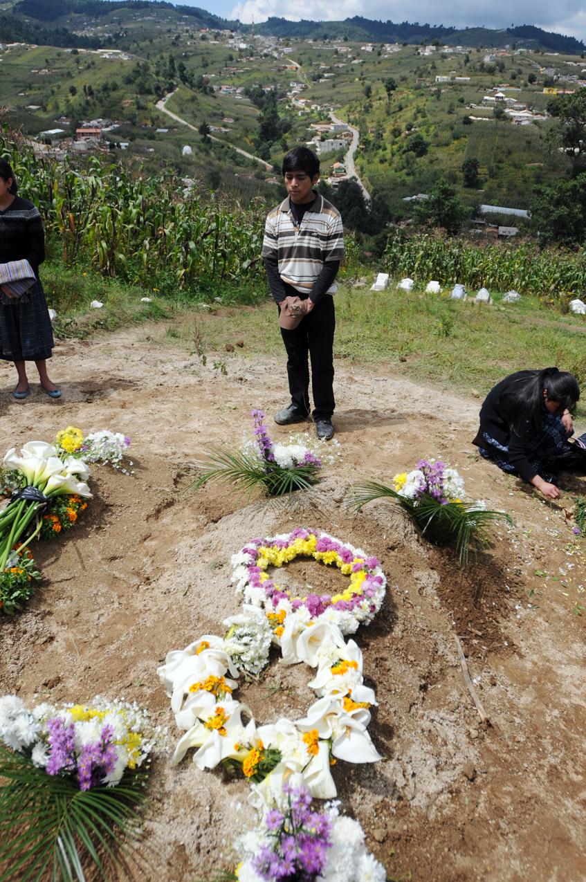 Santos Caxaj, estudiante normalista, visita la tumba de su padre.